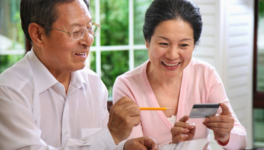 A mature couple looking at their credit card while holding a bill.