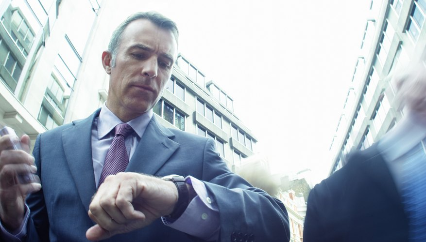 Businessman Looking at his Watch with Blurred People in the Background