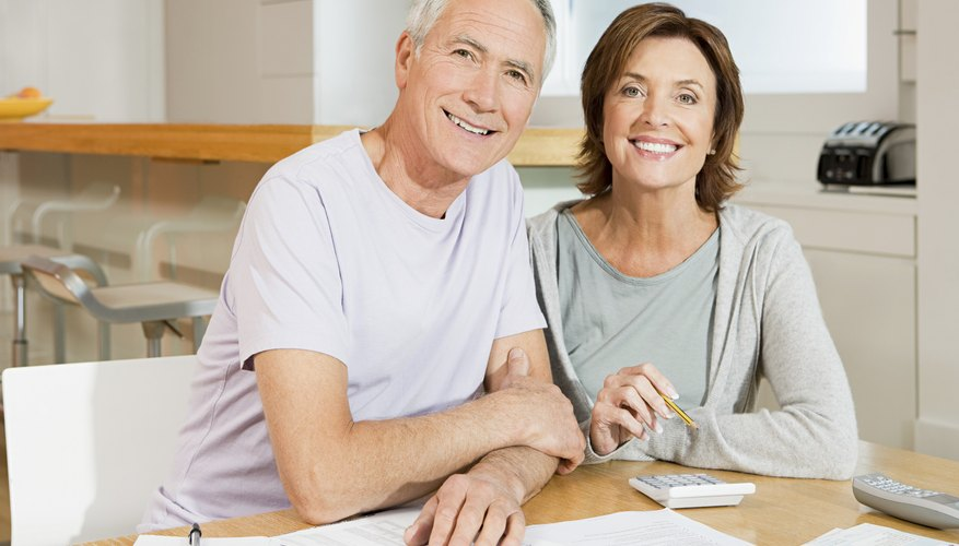Senior couple going over bills with calculator