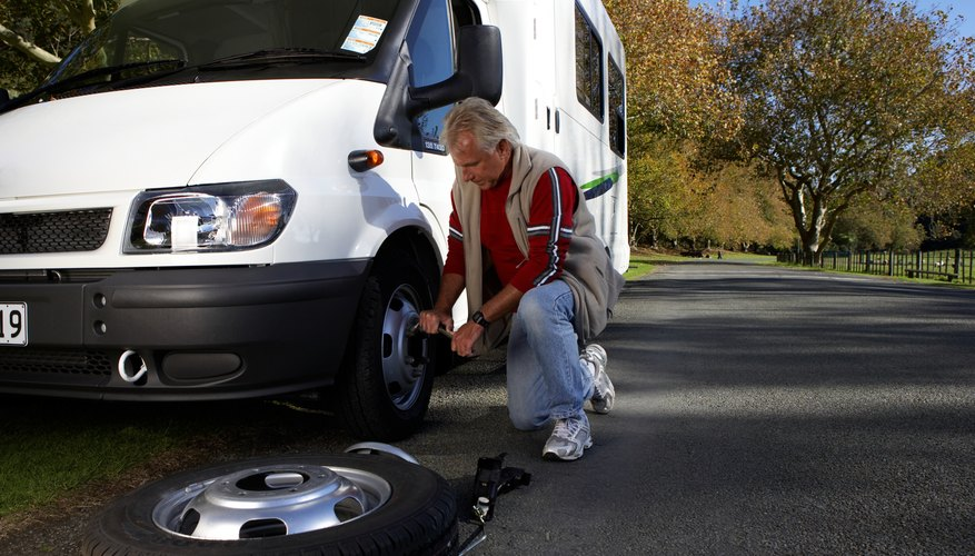Mature man changing tire in motor home at roadside