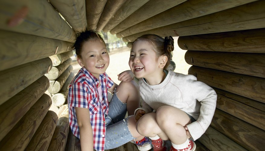 Two Young Girls in a Wooden Tunnel in a Playground