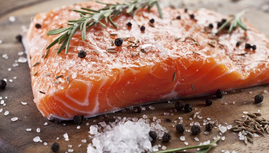 Raw salmon filet with herbs and spices.