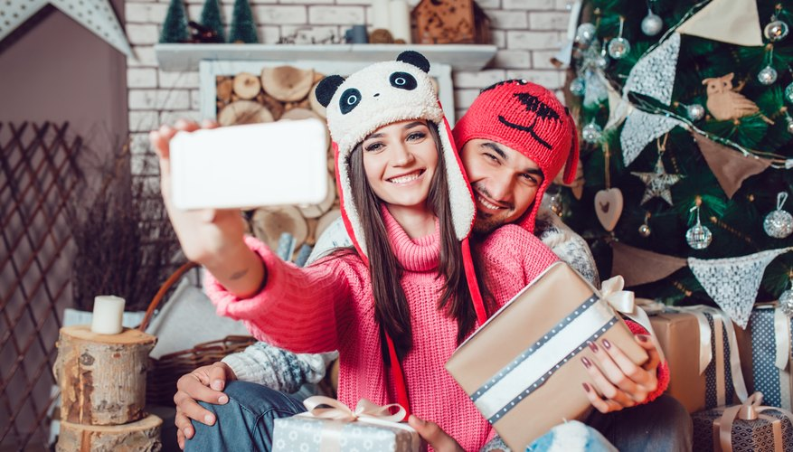 A couple wearing silly hats take selfie.