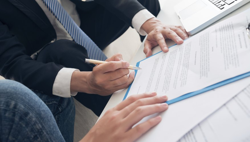 A close-up of a client signing documents with an agent.