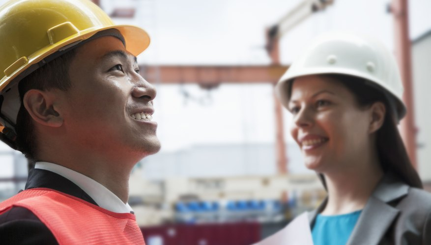Two engineers smiling in protective workwear outside in a shipping yard