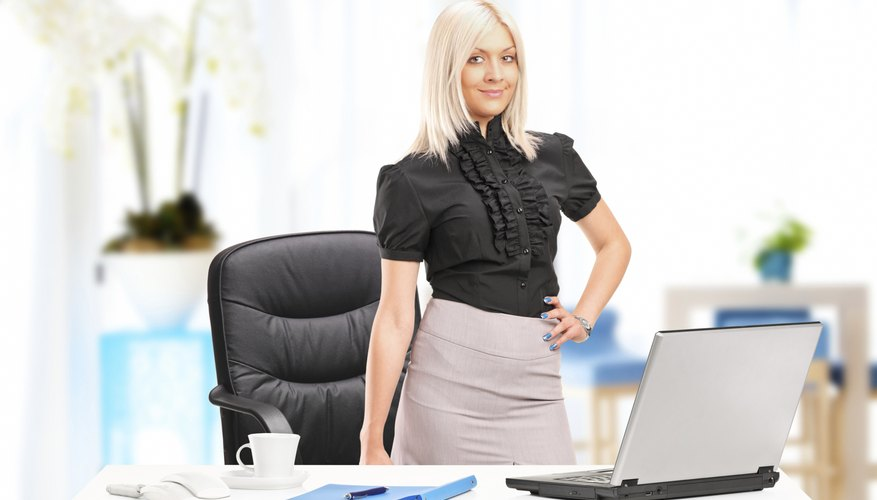 Young businesswoman standing next to desk with laptop