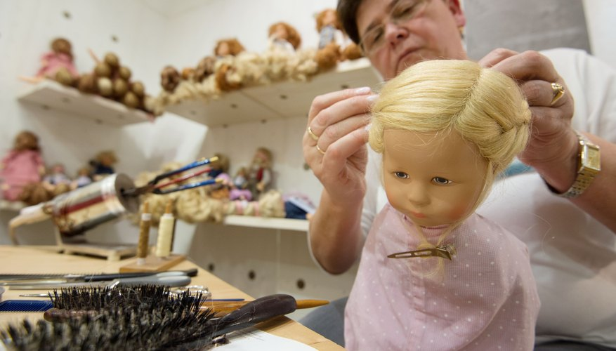 A woman styling a doll's hair in her studio.