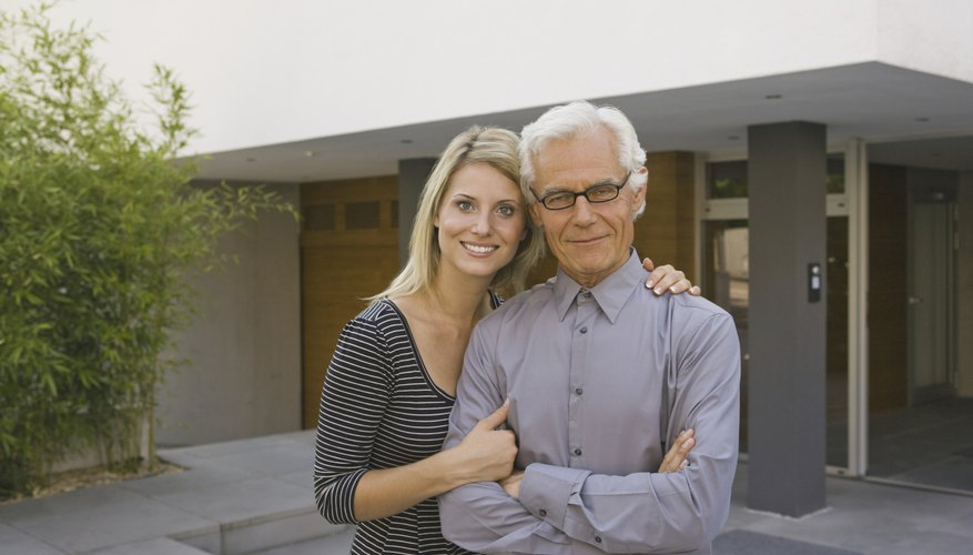 A father and daughter standing in the driveway in front of a home.