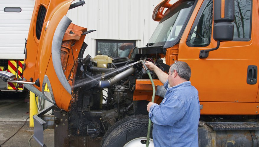 Mechanic washes truck before servicing