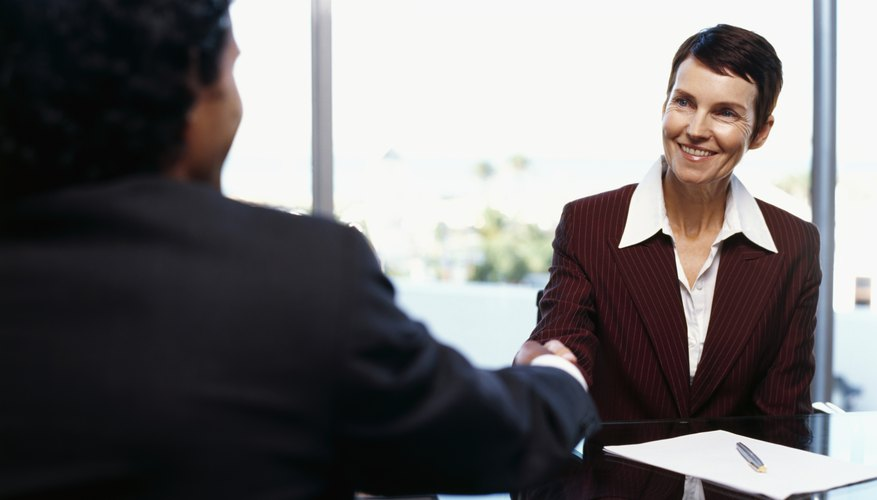 businesswoman and a businessman shaking hands in a conference room