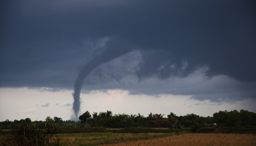 A tornado forms and moves across the ground in the distance.