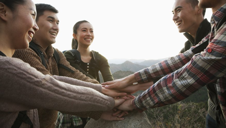 Group of young people smiling and holding hands together on the stone