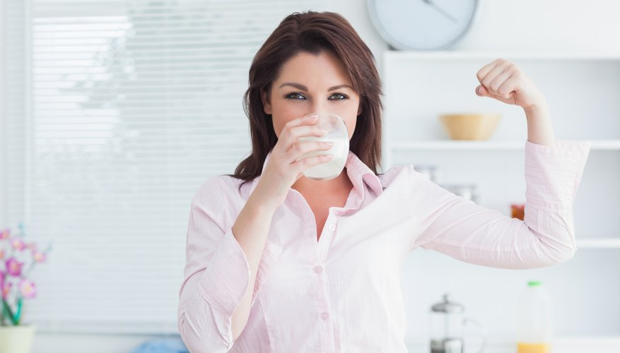 Woman with glass of milk flexing arm.