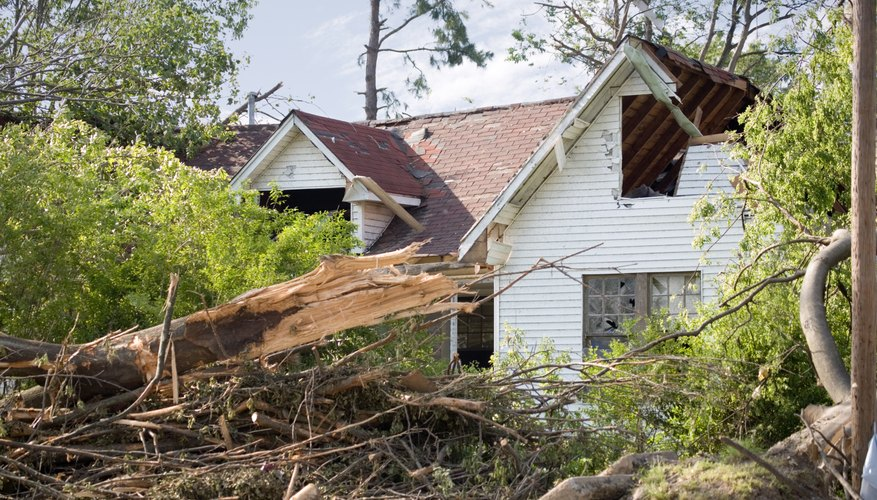A damaged roof and windows of a home after a tornado touches down.