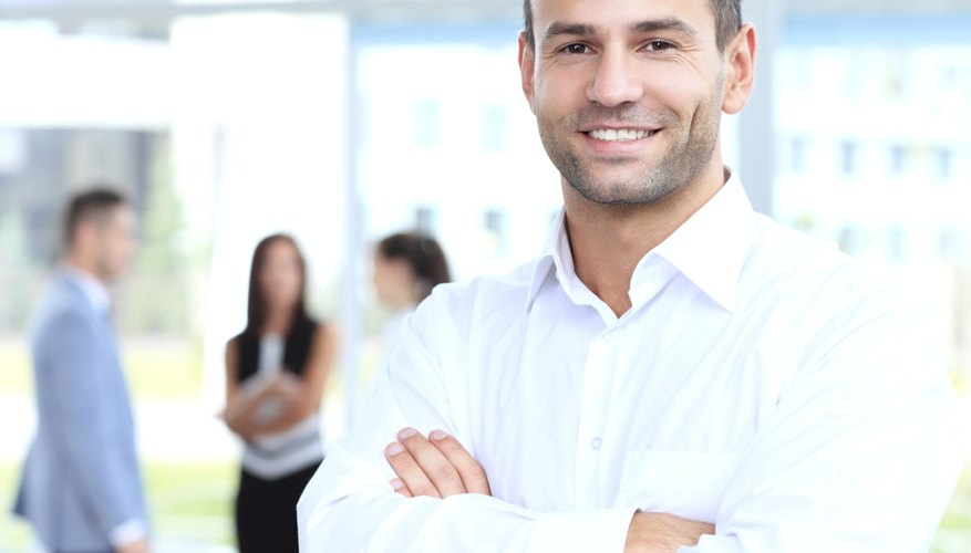 Cross-armed leader looking at camera in working environment