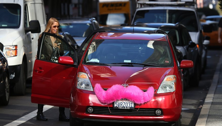 A woman catching a ride from a ridesharing service in the city.