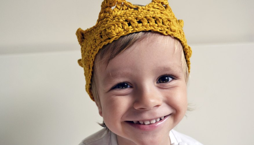 A smiling toddler wearing a knitted crown.