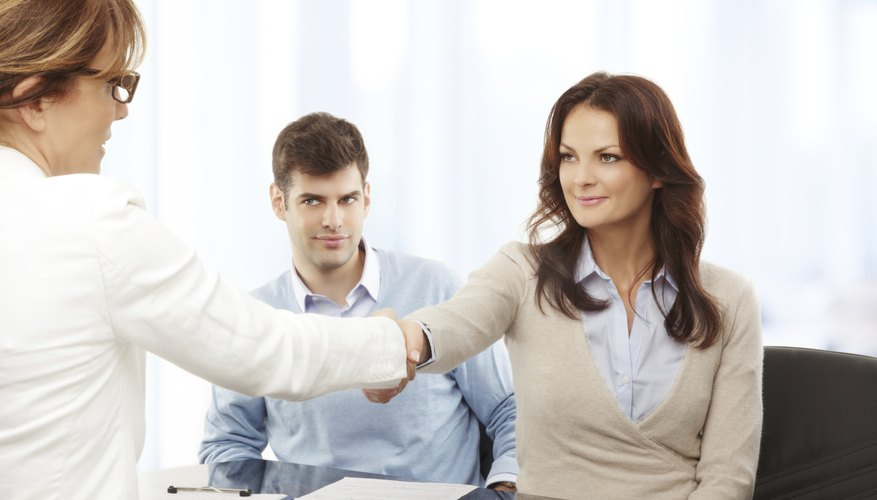 Woman shaking hands with debt collector