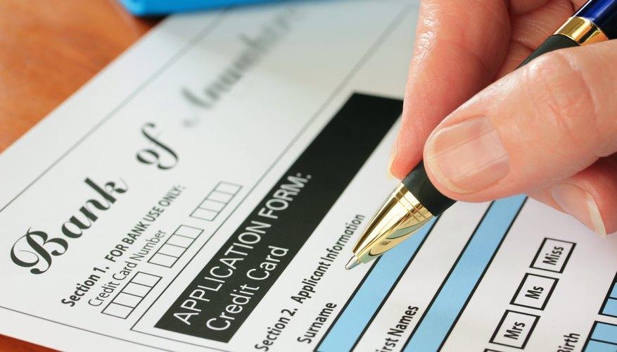 Man using a pen to fill out a credit card application.