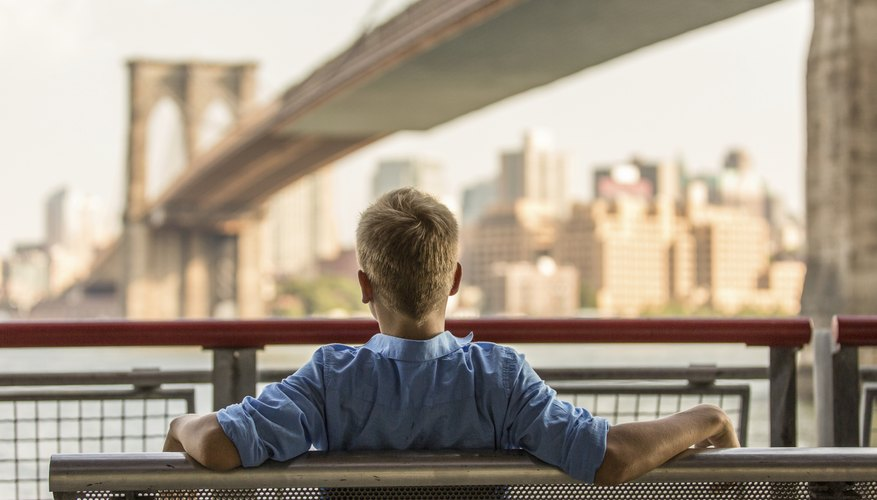 A young boy sits on a bench overlooking a bridge in New York City.