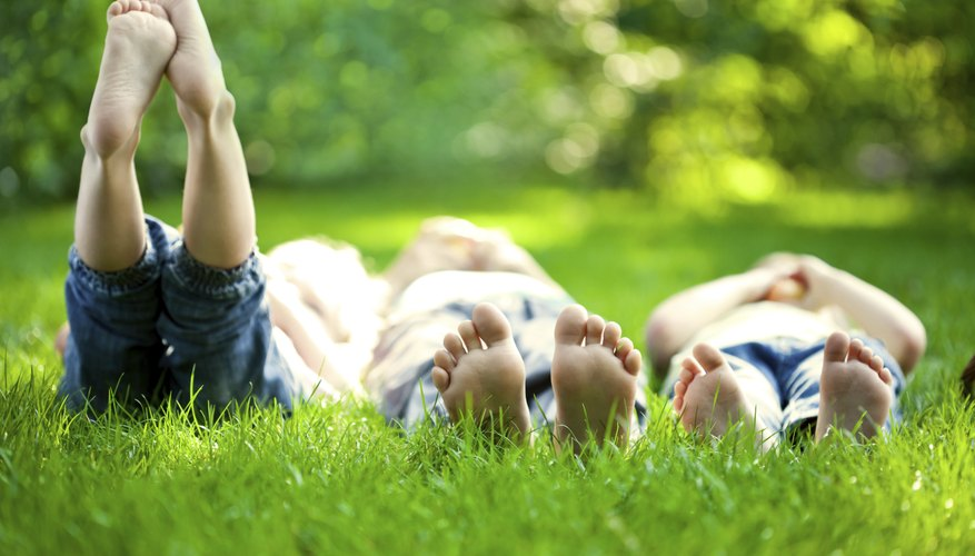 Three young children play in the grass together.