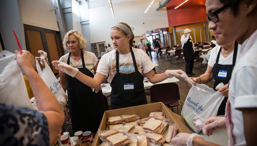 Teenagers pack sandwiches at a food bank.