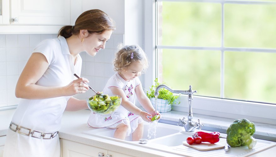Girl and mother washing vegetables in kitchen sink