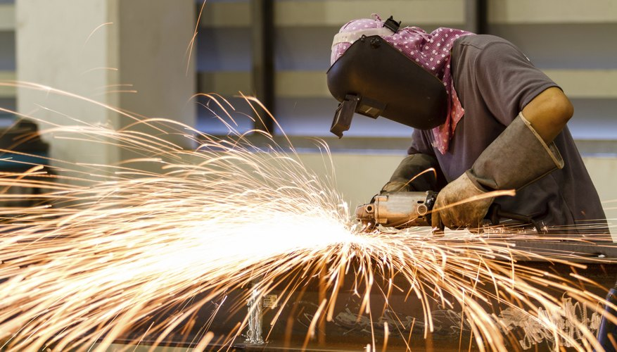 A factory worker using a power grinder on a steel structure
