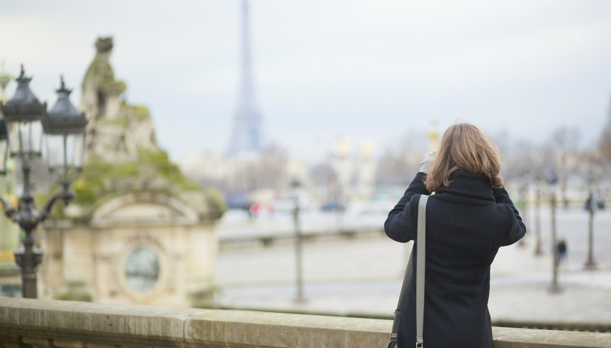 A young woman taking a photograph in Paris.