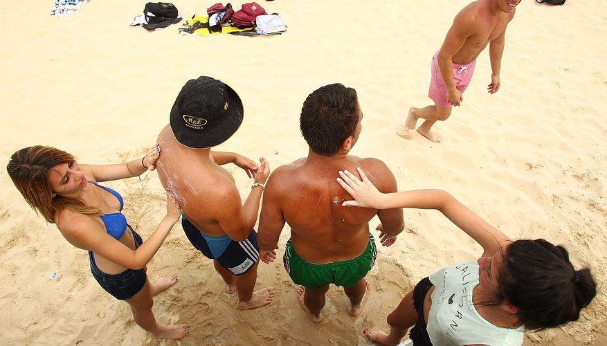 Guys having girls apply sunblock on Bondi Beach near Sydney, Australia