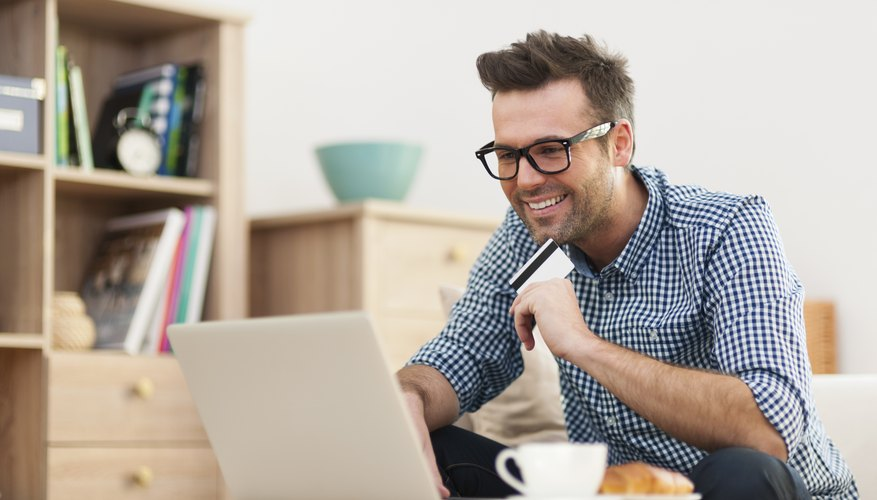 Happy man sitting on sofa with laptop and credit card
