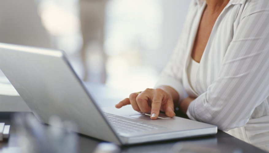 mid section view of a businesswoman using a laptop in an office