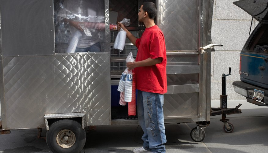 Men stock a food cart in Brooklyn, NY