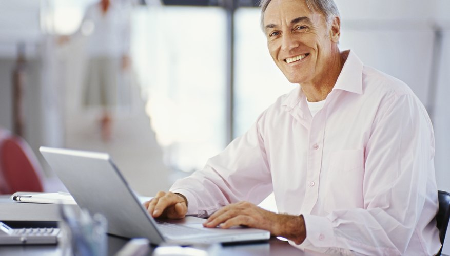 Elderly man researching on laptop in home office.