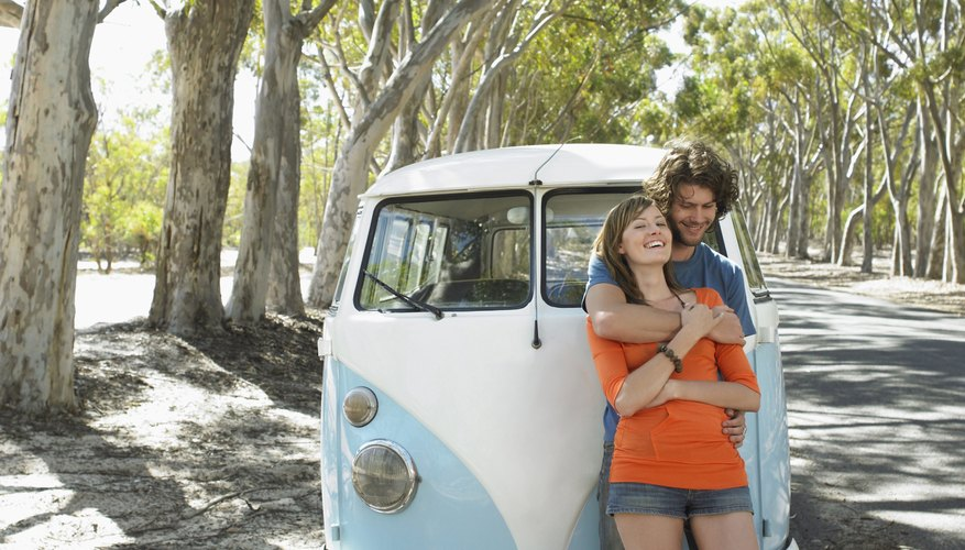 Couple embrace in front of a camper