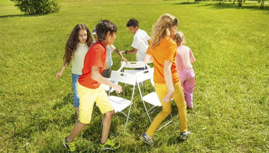 A group of children play musical chairs in the park.