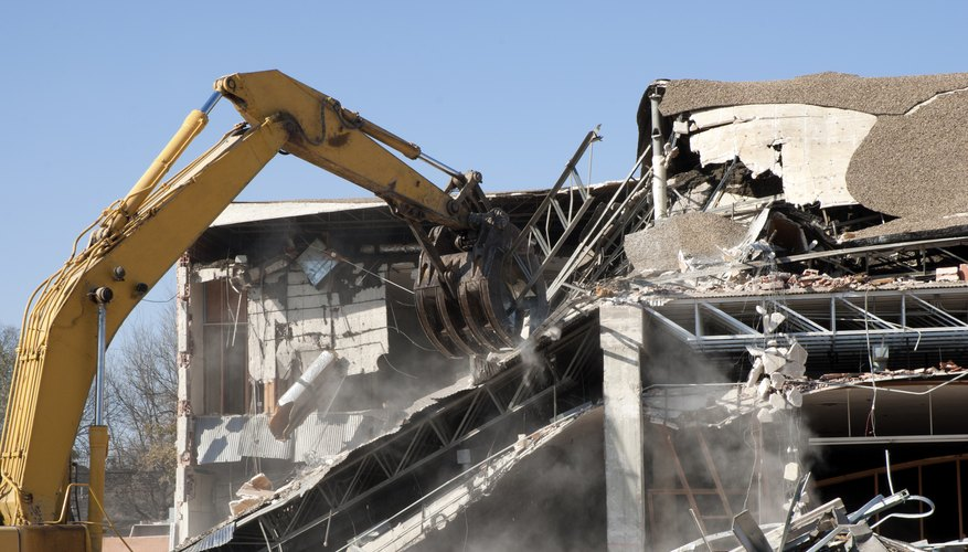 An excavator destroys a building.
