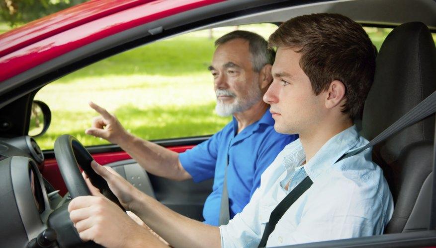 Teen in a car getting driving instructions from a teacher.
