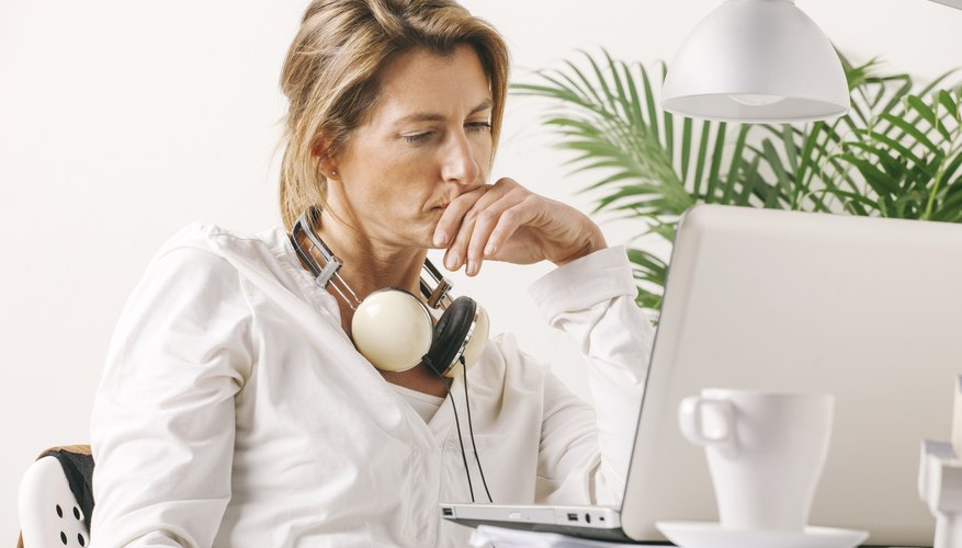 Beautiful mature business woman working with laptop on desk.