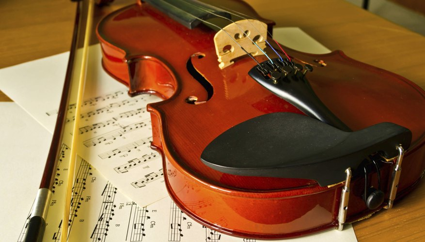 A close-up of a violin, bow and sheet music on a table.
