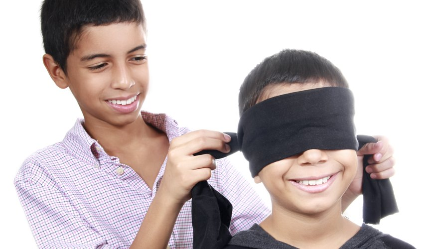 A boy ties a blindfold over the eyes of a yonger boy.