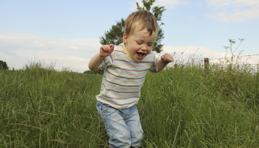 A happy toddler playing in the grass.