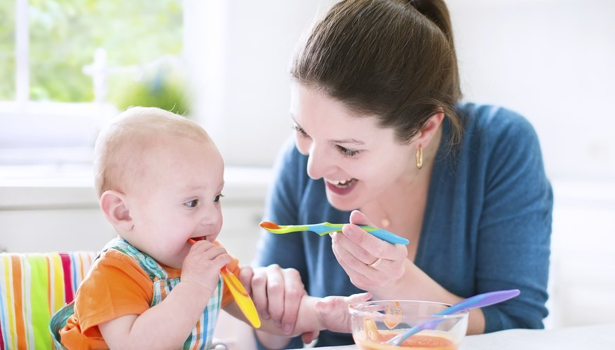 Mother feeding her baby with spoonfuls of vegetables.