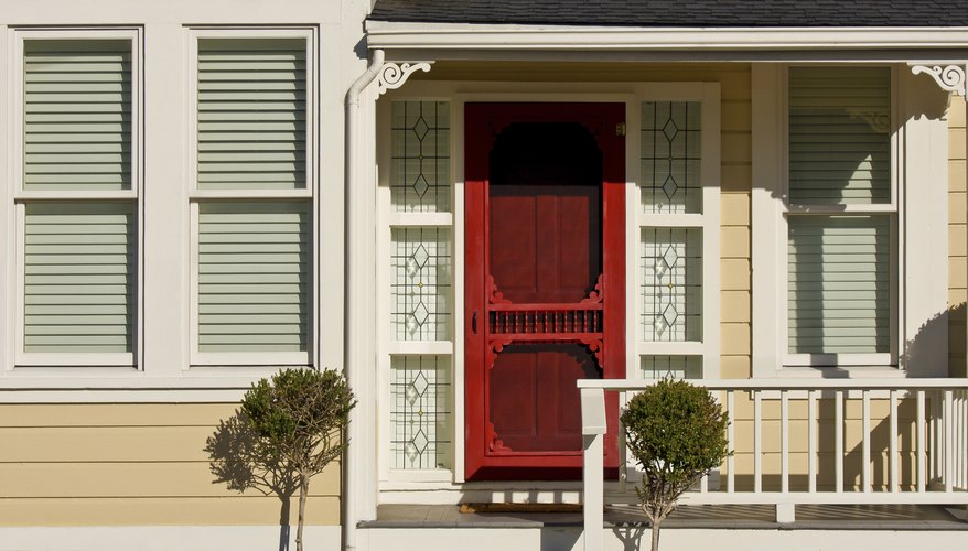 A red wooden door on a sunny porch.