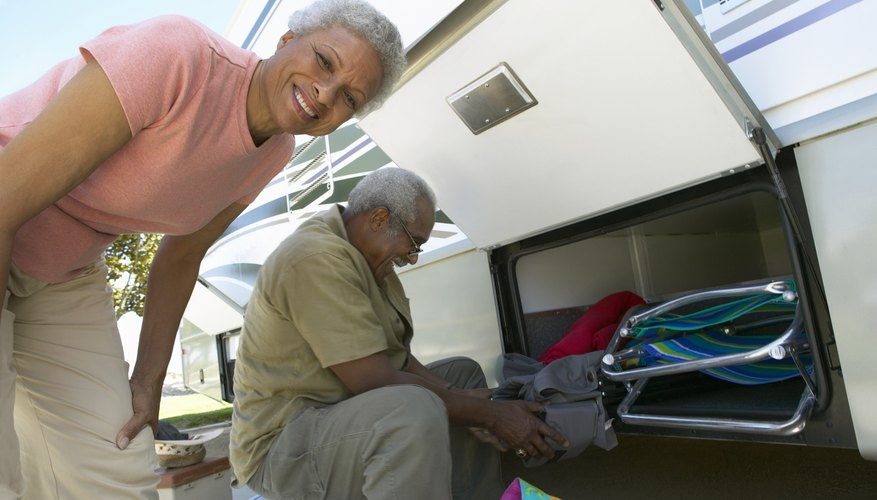 Senior Couple Unload Luggage From Their Motor Home
