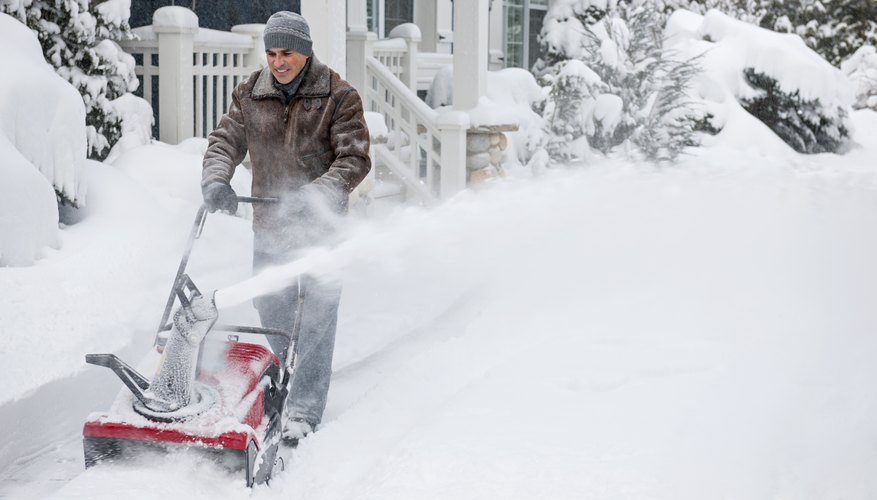 A man clearing his driveway using a single-stage snowblower