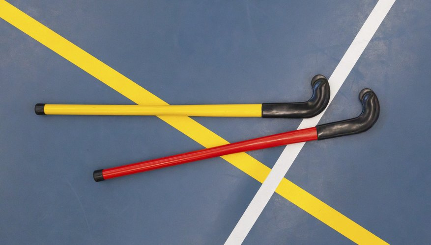 Floor hockey sticks laying on a gym floor.