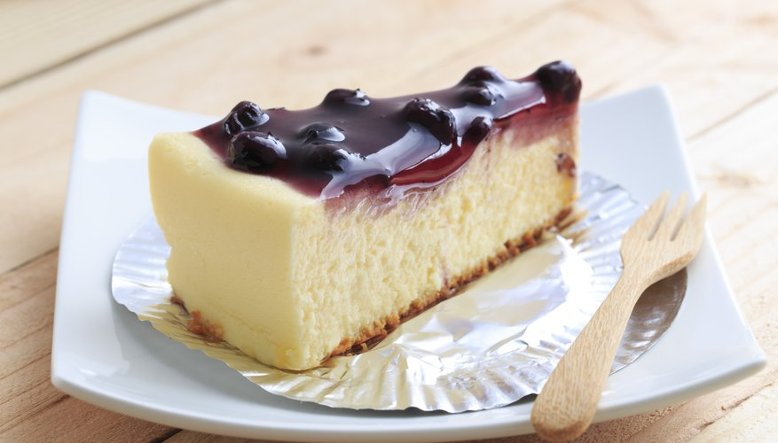A slice of blueberry cheesecake on a wooden table.