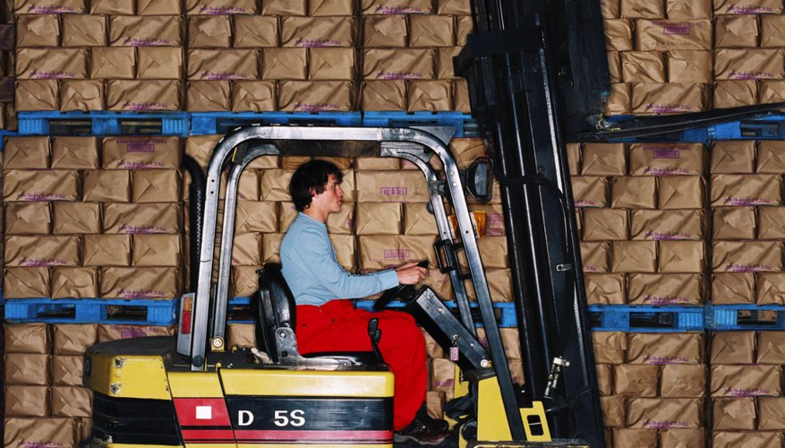 side profile of a young man driving a forklift in a warehouse