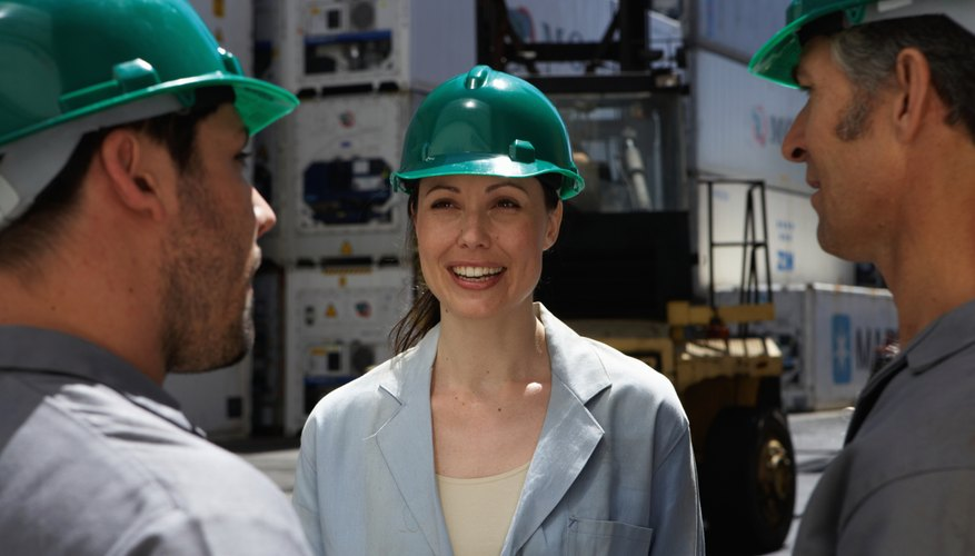 Men and woman standing beside cargo containers, wearing hard hats